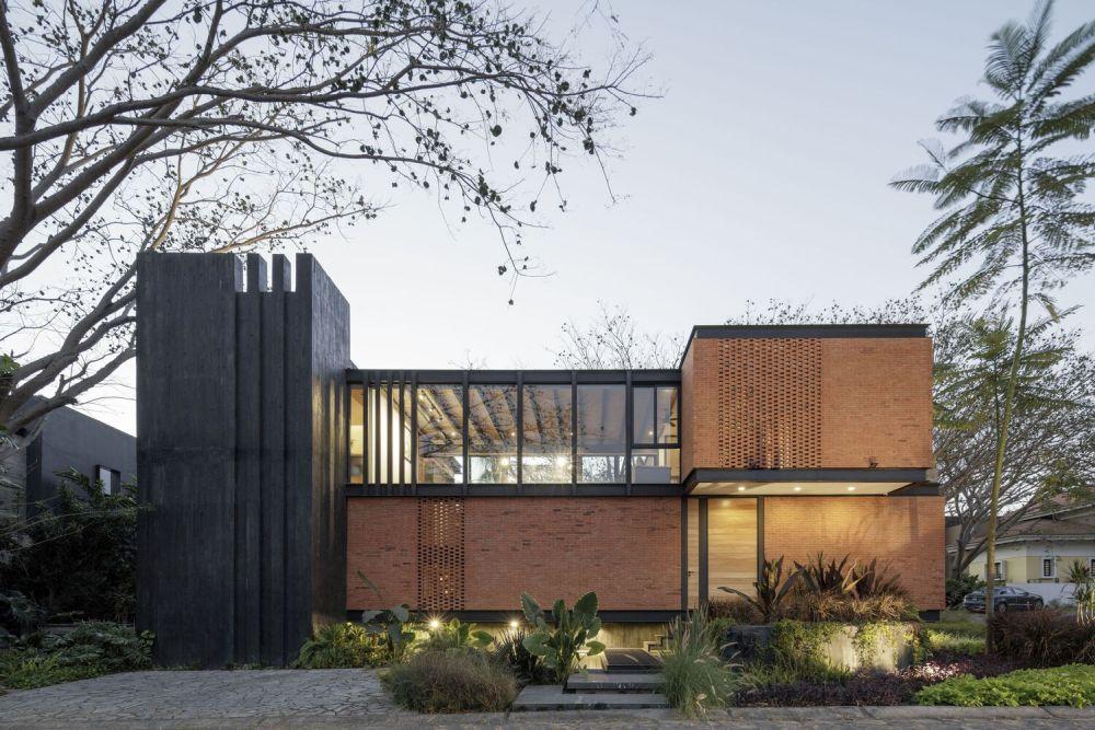 The exterior design alternates between warm brick and dark grey colors