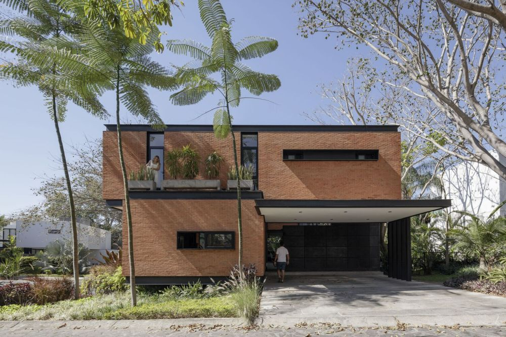 An overhang extends over the driveway and adds depth to this side of the house