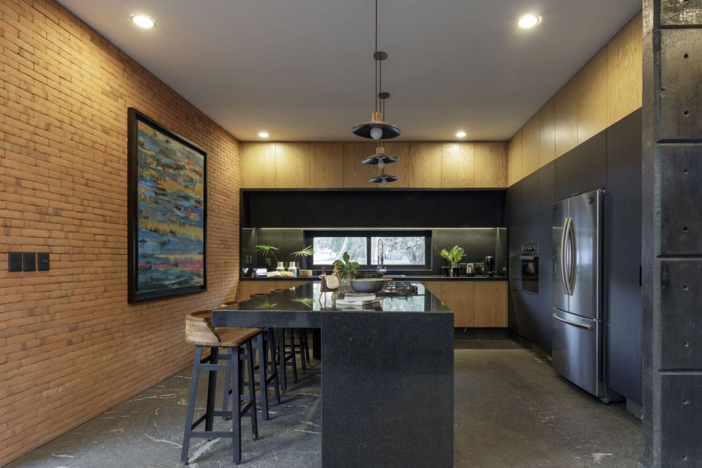 The kitchen is semi-open and has an island which also serves as a bar