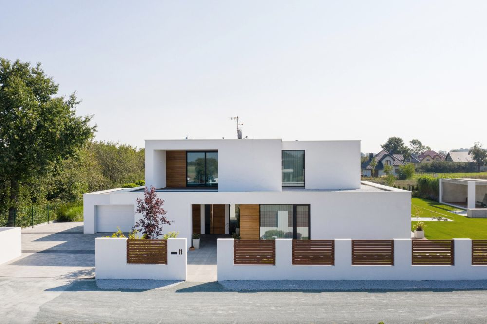 The wooden accents add depth and character to the box-like volumes of the house