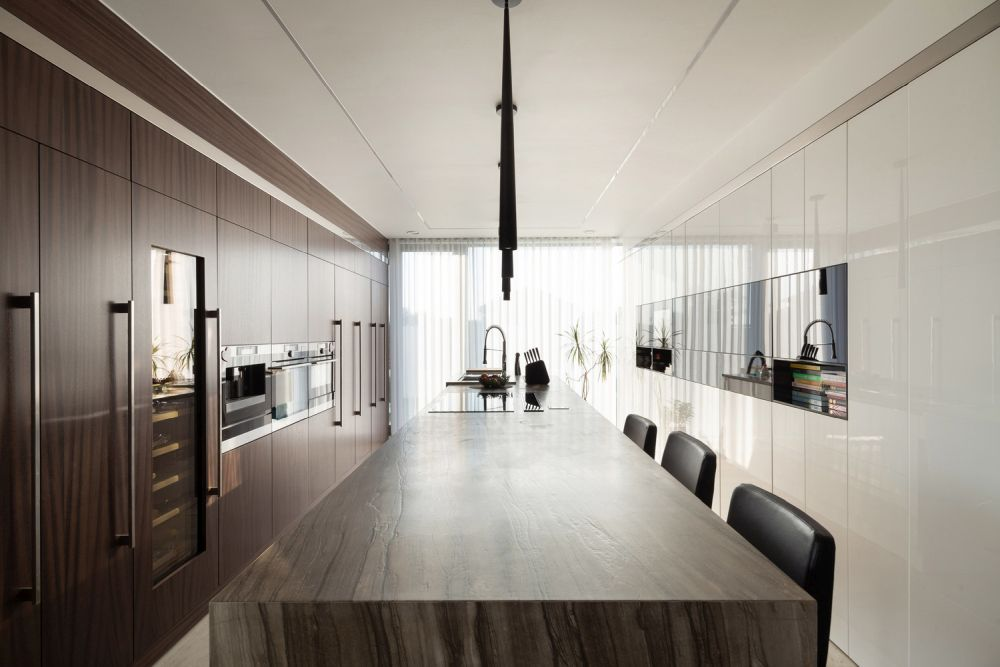 The kitchen has an elongated layout and a big island as a centerpiece
