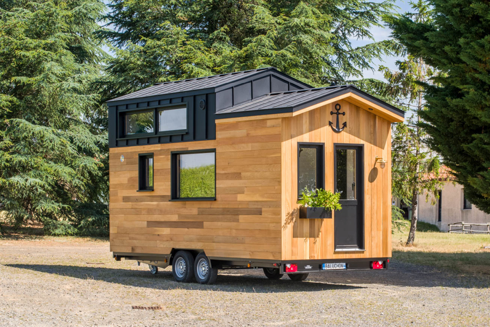 There's multiple windows of different shapes and sizes on each side of this tiny house