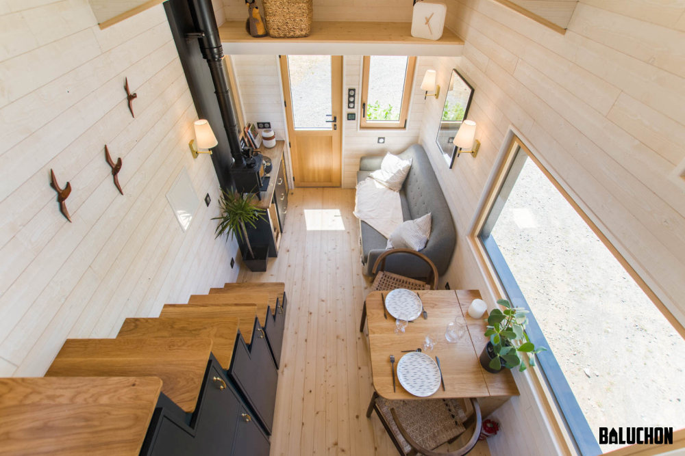 Another reason why this tiny house feels so spacious and inviting is because of the color and texture of the walls