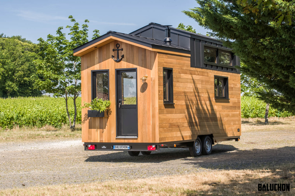 This tiny house features exterior cedar walls and a a black aluminum roof which matches the trailer