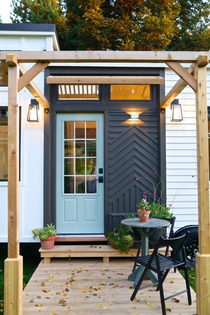 The glass panel front door features a farmhouse-inspired aesthetic