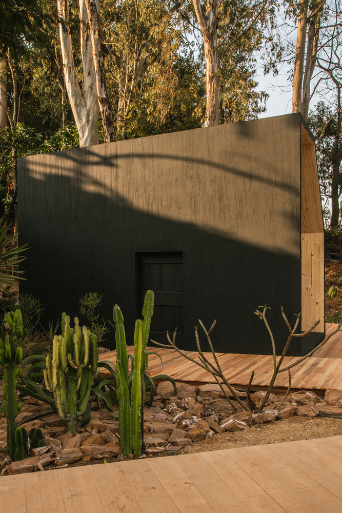 The front facade is minimal and consists of a dark, flat wall with only a door standing out