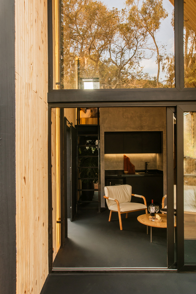 The large windows and doors also expose the interior to the surrounding outdoor areas