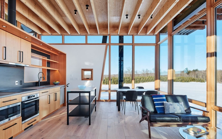 The open kitchen is positioned along the staircase wall and the living and dining area are surrounded by windows