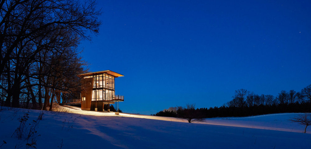 The cabin is strategically positioned at the top of the gently sloping site with a series of large trees behind it
