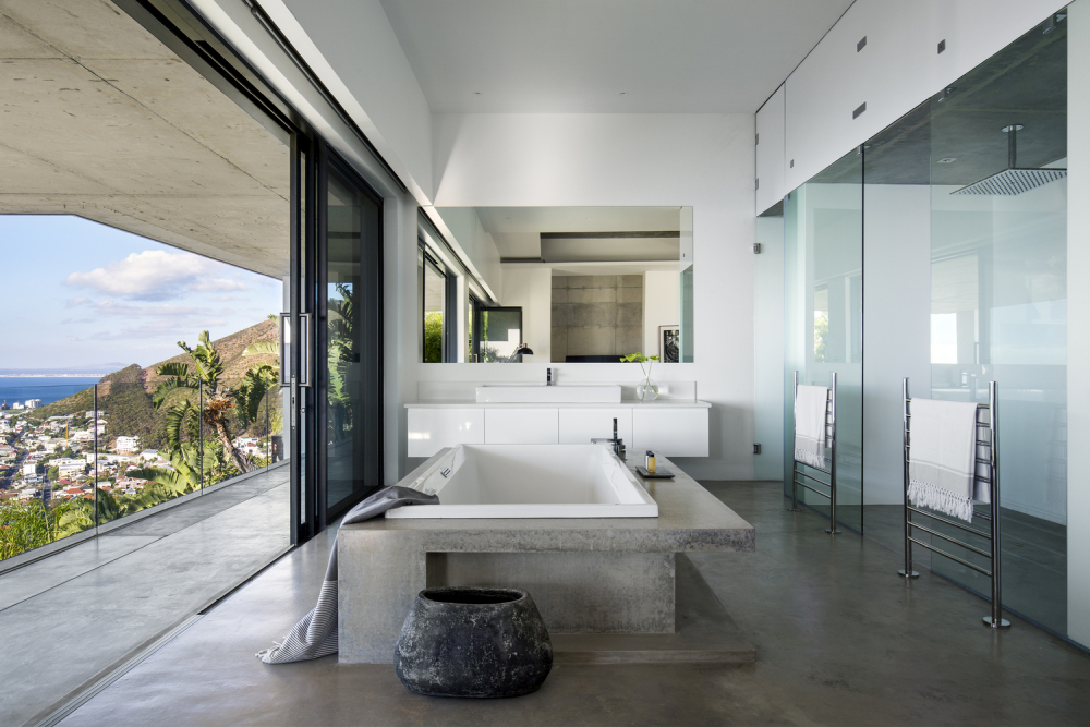 The large master bathroom has a double walk-in shower, a concrete-framed tub and its own terrace