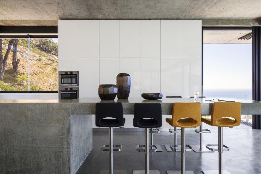 The large concrete kitchen island has bar stool seating on both sides
