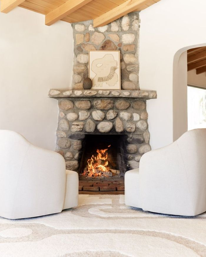 Stone Fireplace with two white armchairs