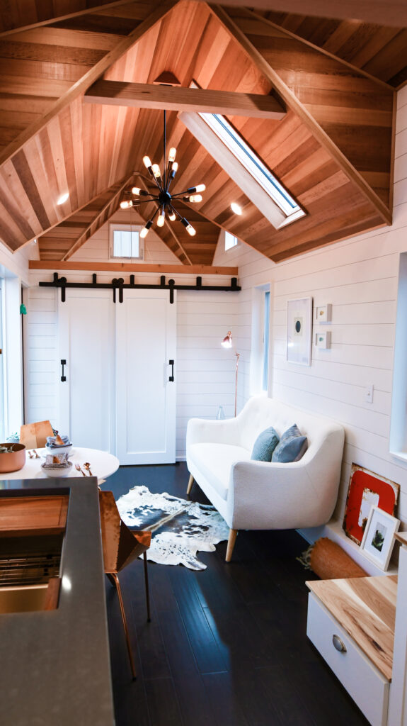 On the right size of the living area is the main bedroom behind these sliding barn doors