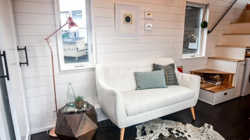 The white horizontal wall boards make the living area look airy and give it a cozy farmhouse vibe