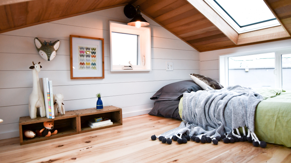 The loft bedroom has a low ceiling with skylights and several additional small windows