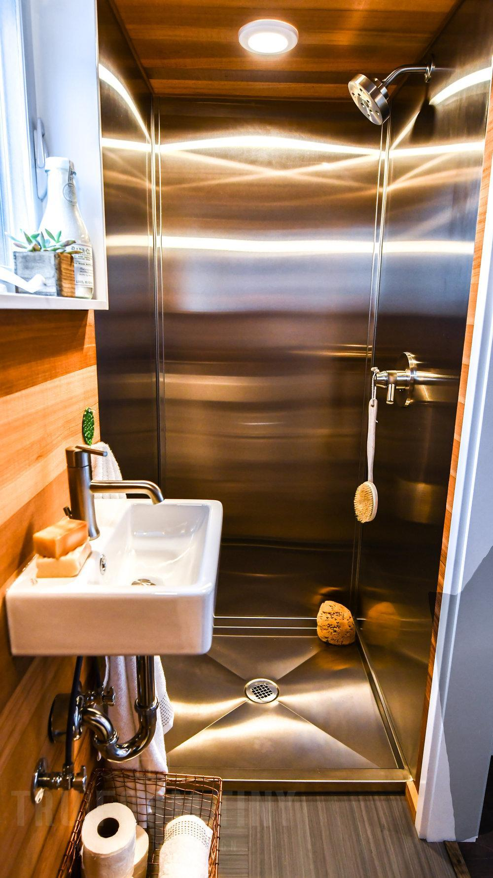 The bathroom includes a custom built-in shower