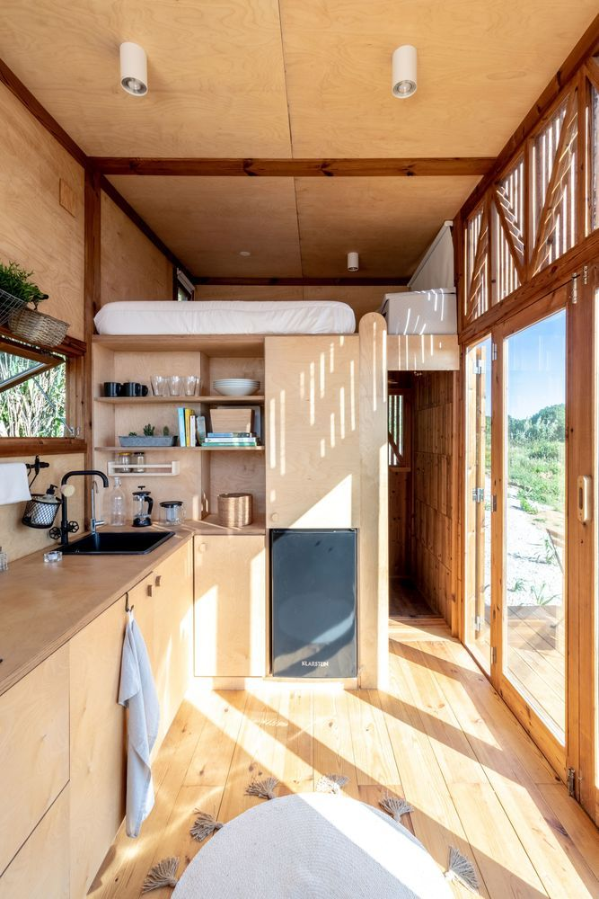This tiny house has two sleeping areas, one of which is a loft bedroom