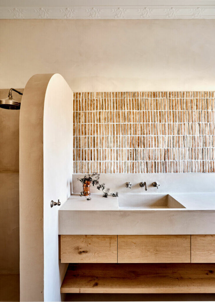 Vertical tiny bricks laying on the bathroom wall above sink