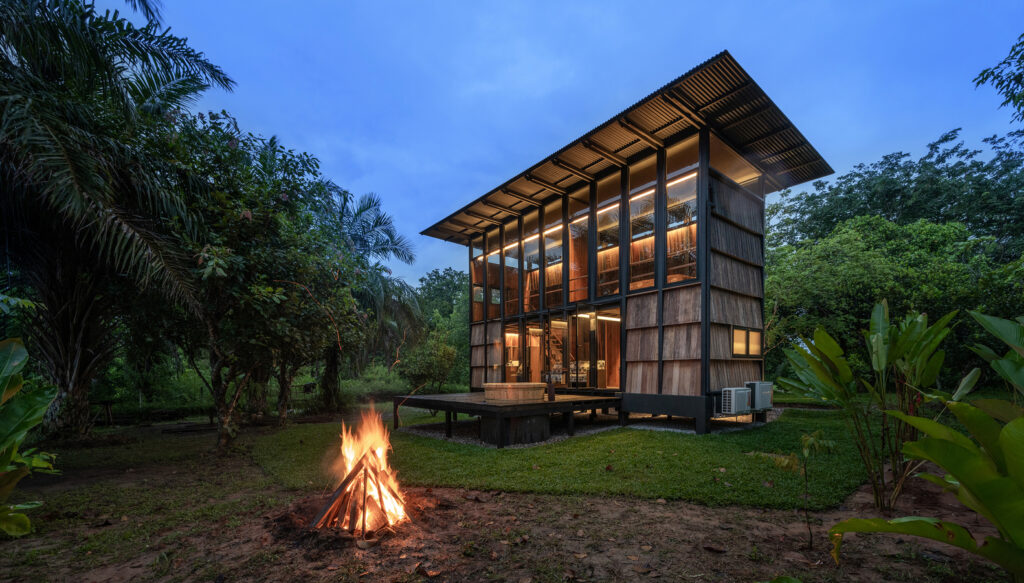 The cabin occupies a small clearing and is surrounded by trees and lush vegetation