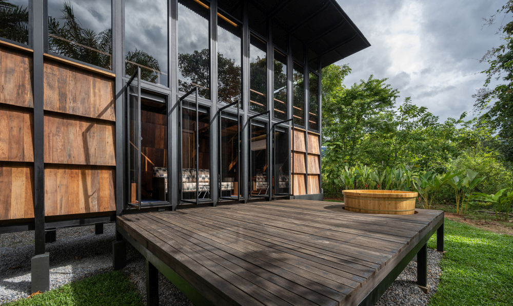 The living area opens onto a raised wooden terrace with uninterrupted views of the surroundings