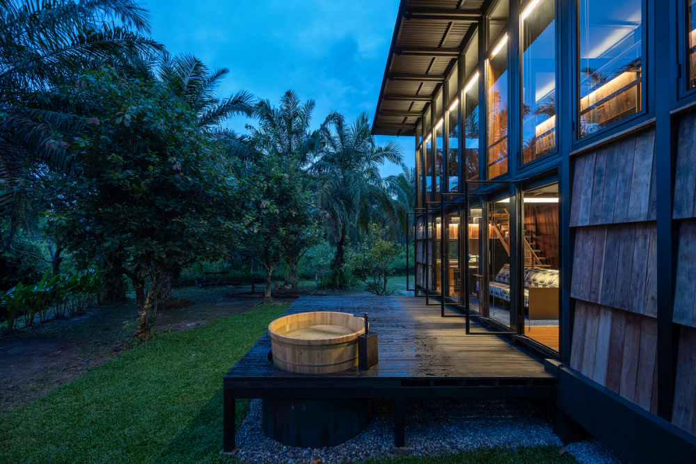 The raised outdoor terrace features a built-in hot tub tucked in one of the corners