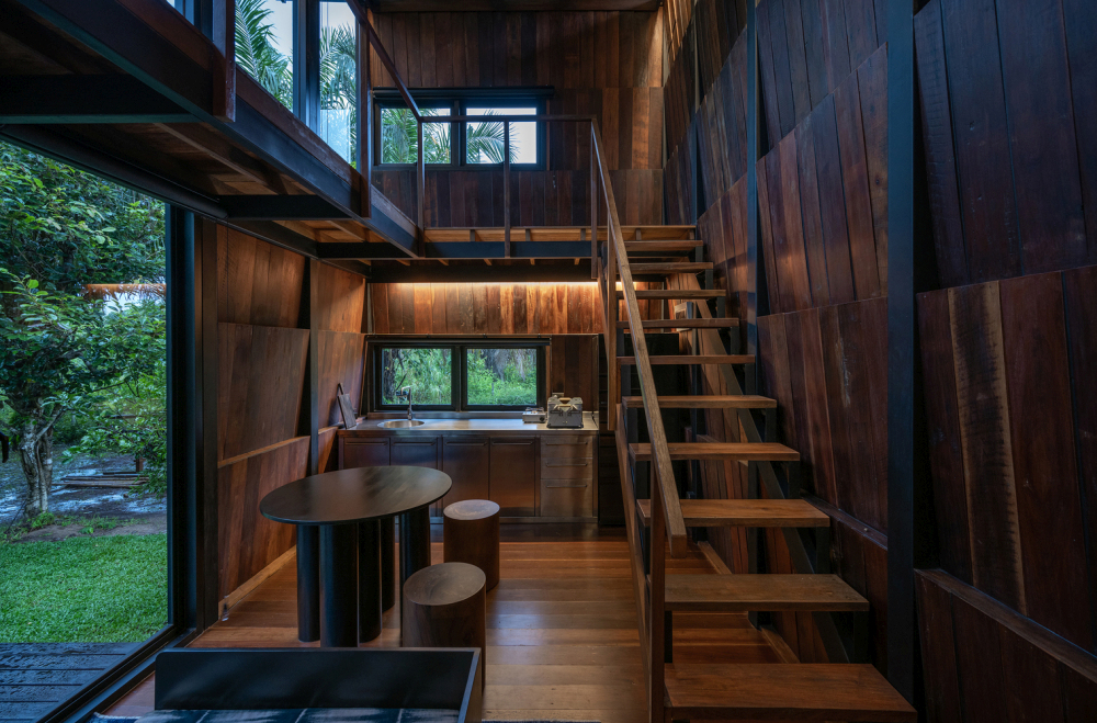 The kitchen is pushed against one of the side walls and partially hidden behind the staircase