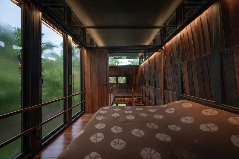 The upper floor bedroom is a full-height space connected to a walkway
