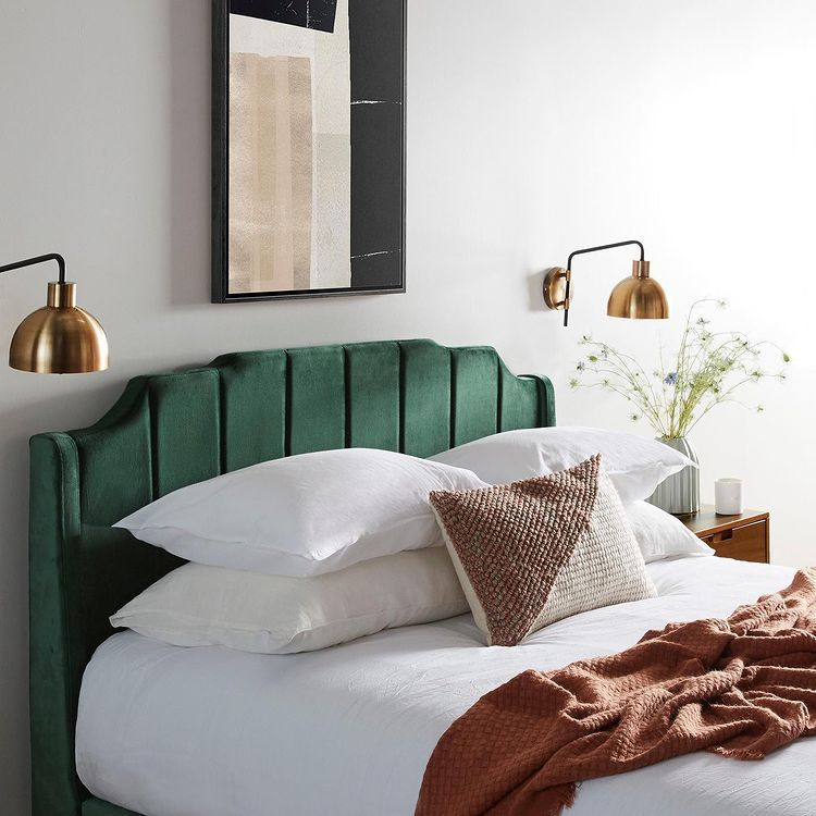 green bed and golden lamps on the wall