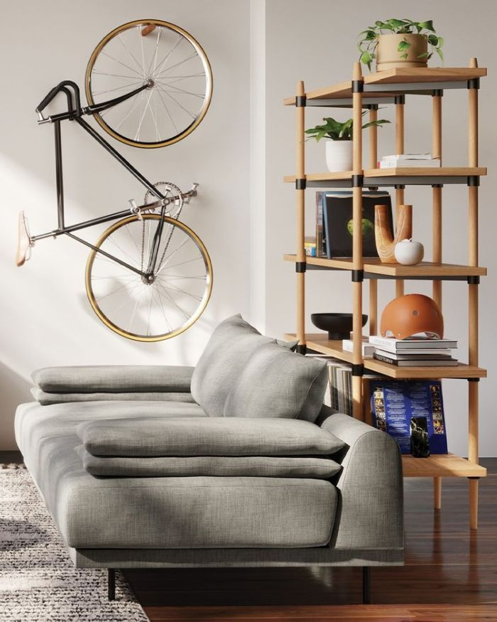 room with gray sofa and bicycle on the wall