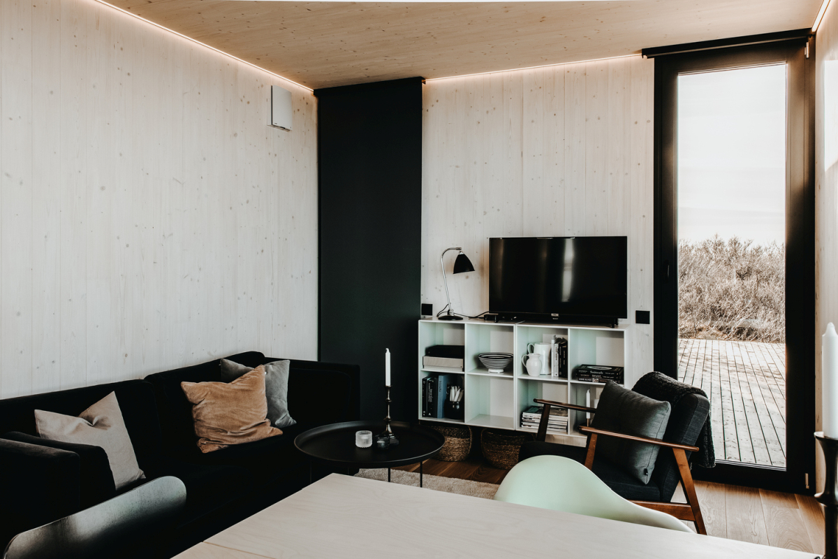 The interior design is kept simple and features light warm neutrals and deep dark furnishings and details