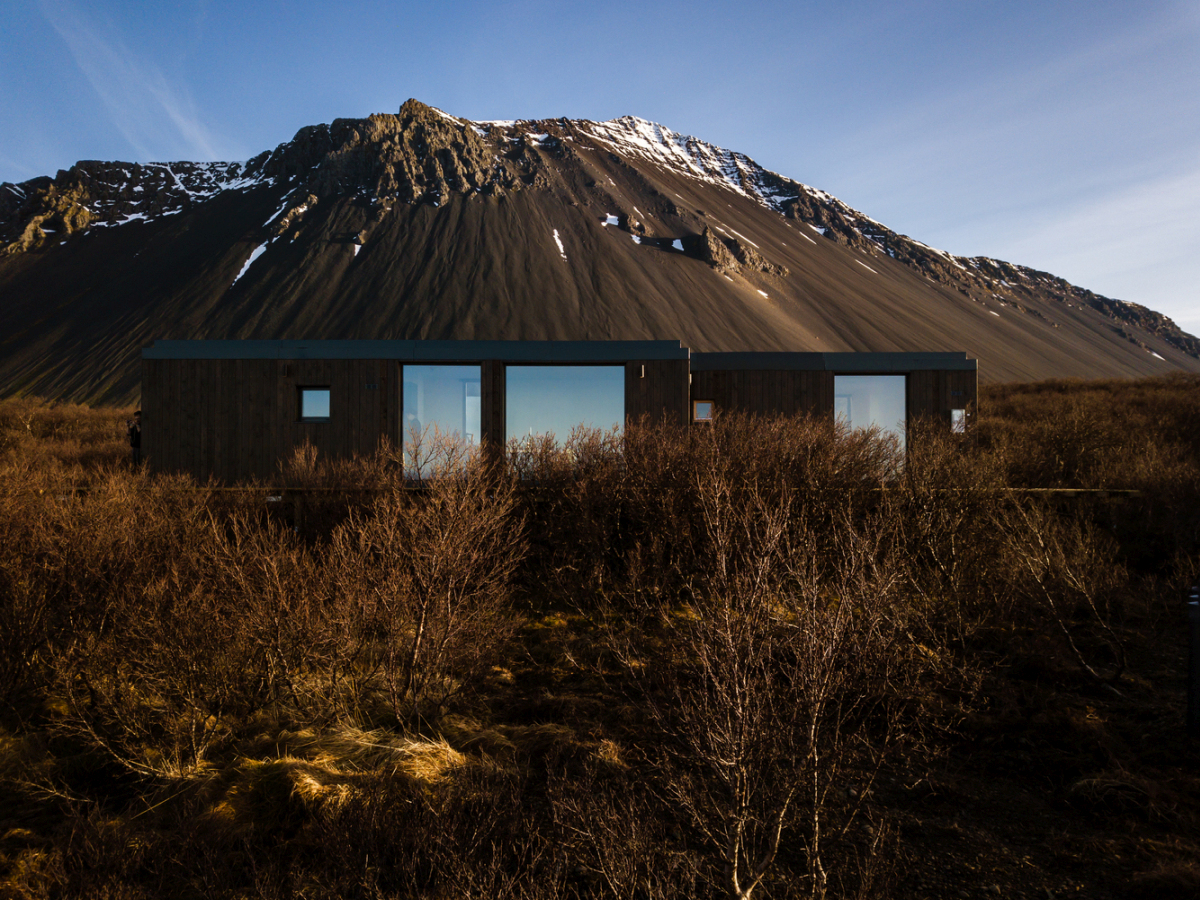The dark wood cladding and flat black roof allow the house to disappear into the landscape