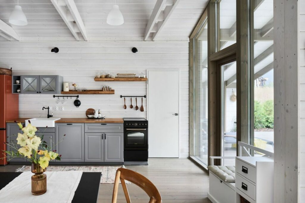 The white wooden roof, walls and beams create a farmhouse-inspired backdrop for the furnishings and decorations